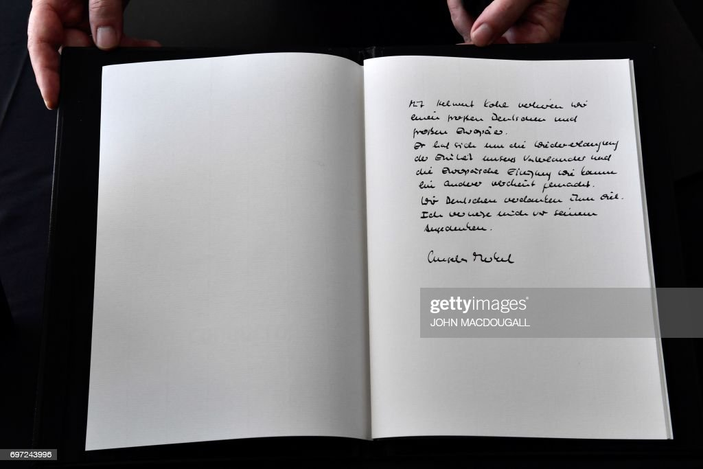 A man holds the book of condolence for former German Chancellor Helmut Kohl with the entry of German Chancellor Angela Merkel at the Chancellery in Berlin on June 18, 2017 - text reads: 'With Helmut Kohl, we have lost a great German and a great Europen. Like hardly any other, he contributed to the unification of our fatherland and of Europe. We Germans have much to thank him for. I bow before his memory'. Helmut Kohl, the former German chancellor who seized the chance to reunite his country after years of Cold War separation, died at the age of 87 on June 16, 2017. / AFP PHOTO / John MACDOUGALL