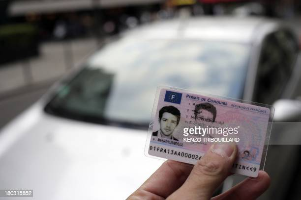A man holds the first French smart card driver's license in front of a car on September 11 2013 in Paris This secured new driver's license...