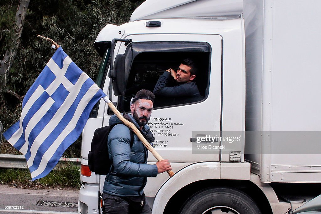A man holds the Greek flag as clashes break out on the highway after police blocked the road from a planned pension reform protest outside the Agriculture ministry on February 12, 2016 in Athens, Greece. Around reportedly 800 protesters from Crete gathered outnumbering police who were armed with teargas.