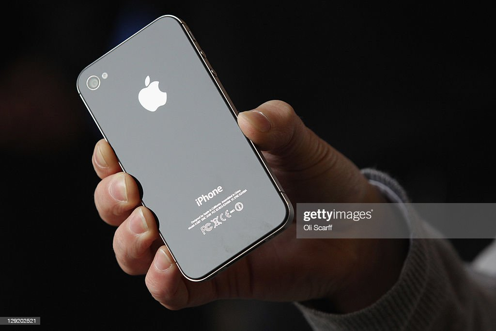 A man holds the new iPhone 4S after being one of the first customers in the Apple store in Covent Garden on October 14, 2011 in London, England. The widely anticipated new mobile phone from Apple has seen customers queue in cities around the world for hours to be amongst the first to buy the device.
