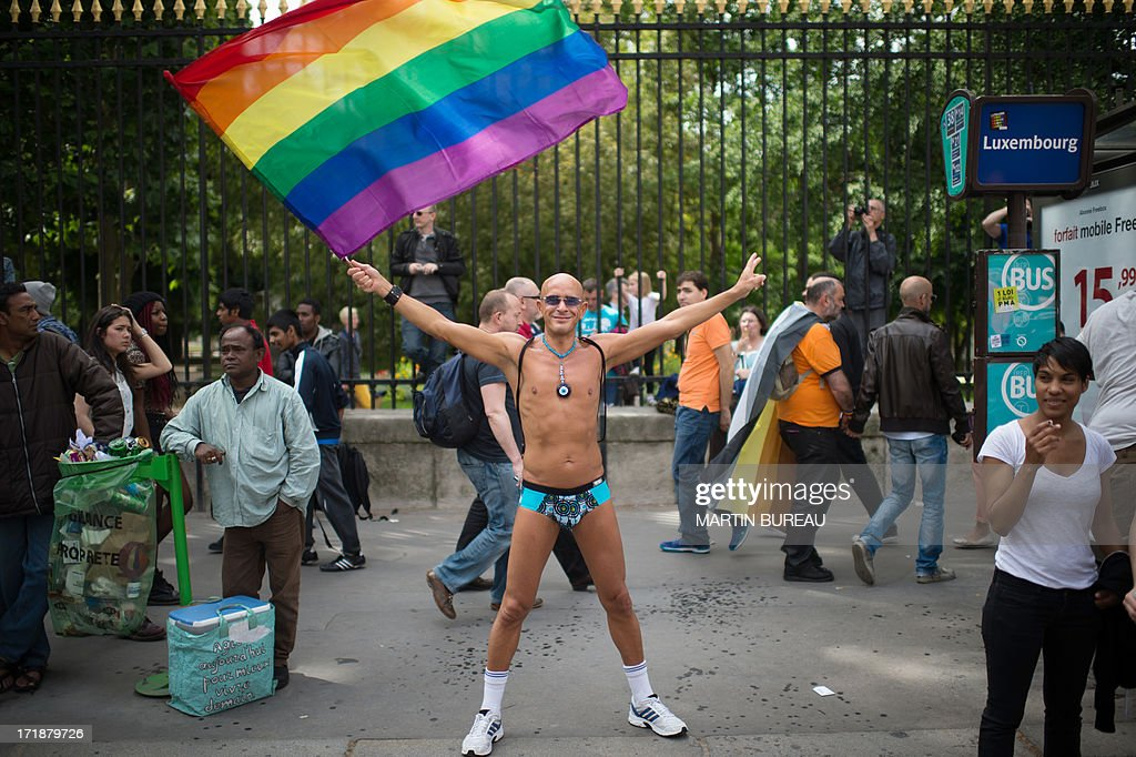 A man holds the rainbow flag, colors of pride for the gay community as people parade during the homosexual, lesbian, bisexual and transgender (HLBT) visibility march, the Gay Pride, on June 29, 2013 in Paris, exactly one month to the day since France celebrated its first gay marriage. AFP PHOTO / MARTIN BUREAU