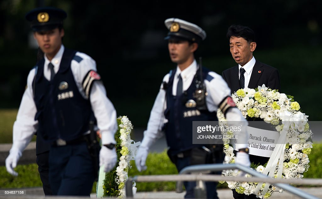A man holds the wreath of US President Obama at the Hiroshima Peace Memorial in Hiroshima on May 27, 2016. US President Barack Obama was to make history later on May 27 when he travels to Hiroshima -- becoming the first sitting US leader to visit the site that ushered in the age of nuclear conflict. / AFP / JOHANNES