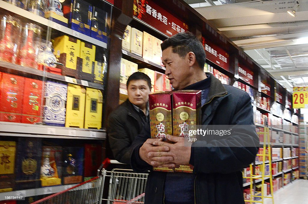 A man holds two bottles of white spirit as he walks in a supermarket in Beijing on November 20, 2012. China Alcoholic Drinks Association said all Chinese 'White spirit' had plasticizer.