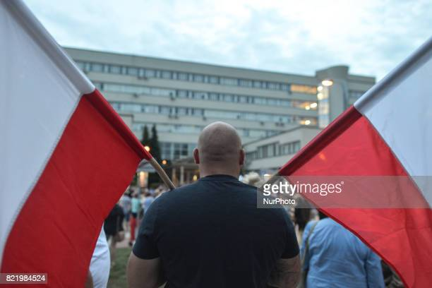 A man holds two Polish national flags during an antigovernment candlelit vigil in front of Krakow's District Court on Monday evening where hundreds...