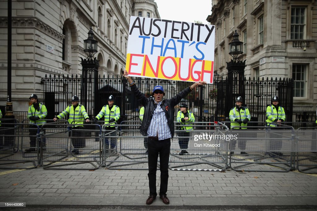 A man holds up a banner reading 'Austerity - That's Enough' outside outside Number 10 Downing Street during a TUC march in protest against the government's austerity measures on October 20, 2012 in London, England. Thousands of people are taking part in the Trades Union Congress (TUC) organised anti-cuts march that ends with a rally in Hyde Park, where Labour leader Ed Miliband is scheduled to address the demonstrators.