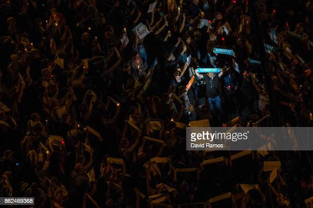 A man holds up a banner that it reads 'llibertat' Freedom in Catalan as he protests against imprisonment of two key members of the Catalan...