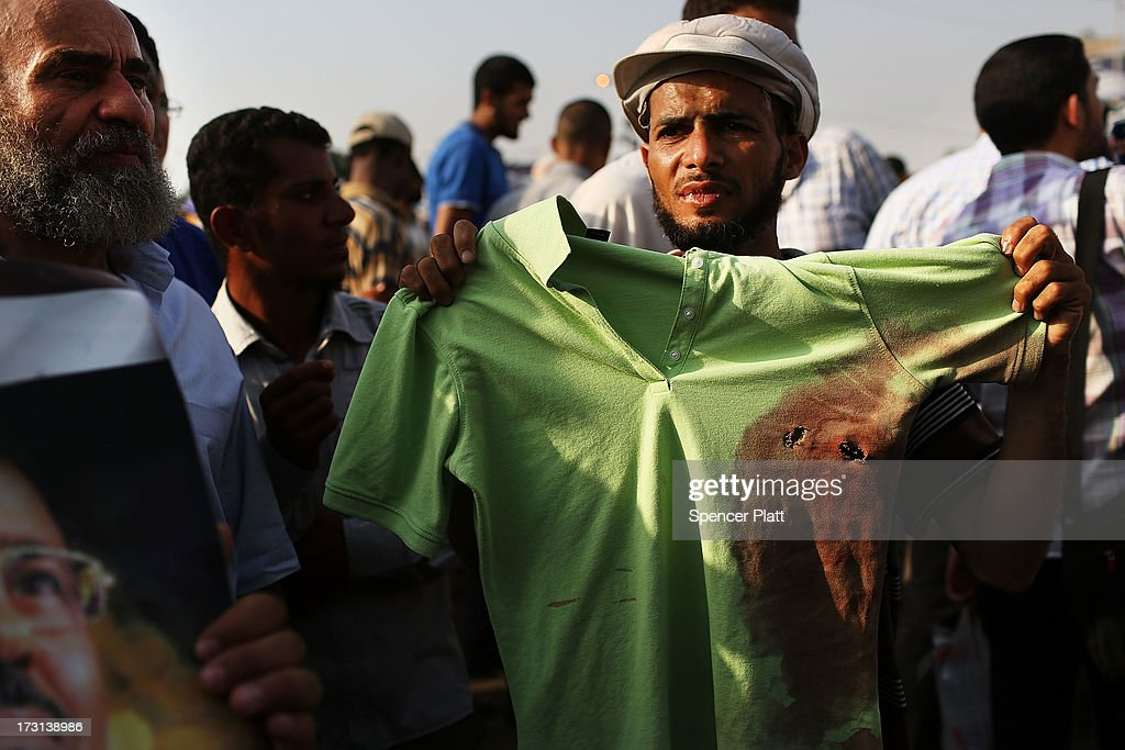 A man holds up a bloodied shirt with bullet holes at a pro Mohamed Morsi rally near where over 50 were purported to have been killed by members of the Egyptian military and police in early morning clashes on July 8, 2013 in Cairo, Egypt. The military, which took over control of the country from Muslim Brotherhood leader Morsi last week, has denied that they opened fire on the protesters and claim the shootings resulted after they came under attack from members of the Muslim Brotherhood. Egypt continues to be in a state of political paralysis following the ousting of Morsi by the military. Adly Mansour, chief justice of the Supreme Constitutional Court, was sworn in as the interim head of state in a ceremony in Cairo on the morning of July 4.