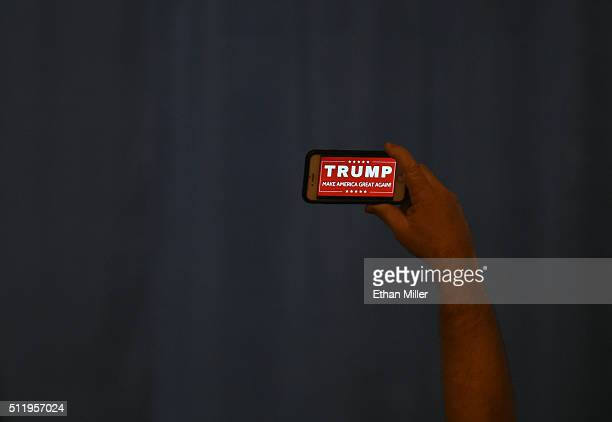 A man holds up a cell phone with a Donald Trump slogan on it while waiting for Republican presidential candidate Donald Trump to speak at a caucus...