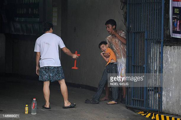 A man holds up a cross towards hostage taker Remer Parparan as he points an icepick against 10 years old Jason Pineda during a hostage taking...