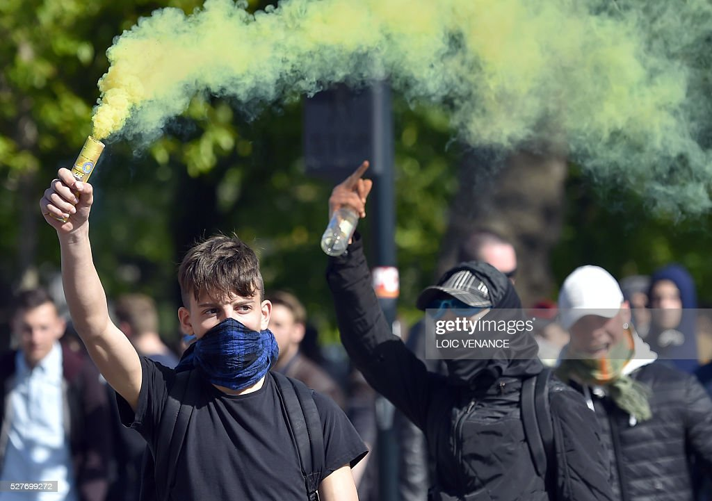 A man holds up a flare during a protest against the government's planned labour law reforms, on May 3, 2016 in Nantes, western France. High school pupils and workers protest against deeply unpopular labour reforms that have divided the Socialist government and raised hackles in a country accustomed to iron-clad job security. / AFP / LOIC