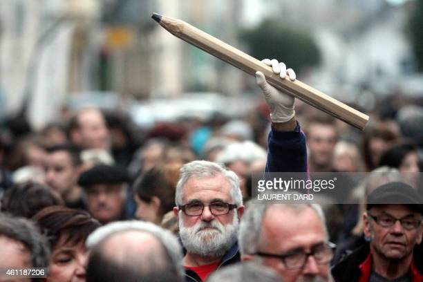 A man holds up a giant pencil during a gathering in Tarbes southern France on January 8 in tribute to the 12 people killed the day before by two...