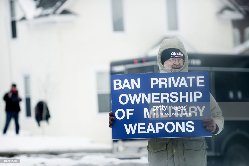 A man holds up a gun control sign while US President Barack Obama's motorcade passes on the way to the Minneapolis Police Department's special operations center February 4, 2013 in Minneapolis, Minnesota. Obama met with local leaders and law enforcement to discus gun violence. AFP PHOTO/Brendan SMIALOWSKI