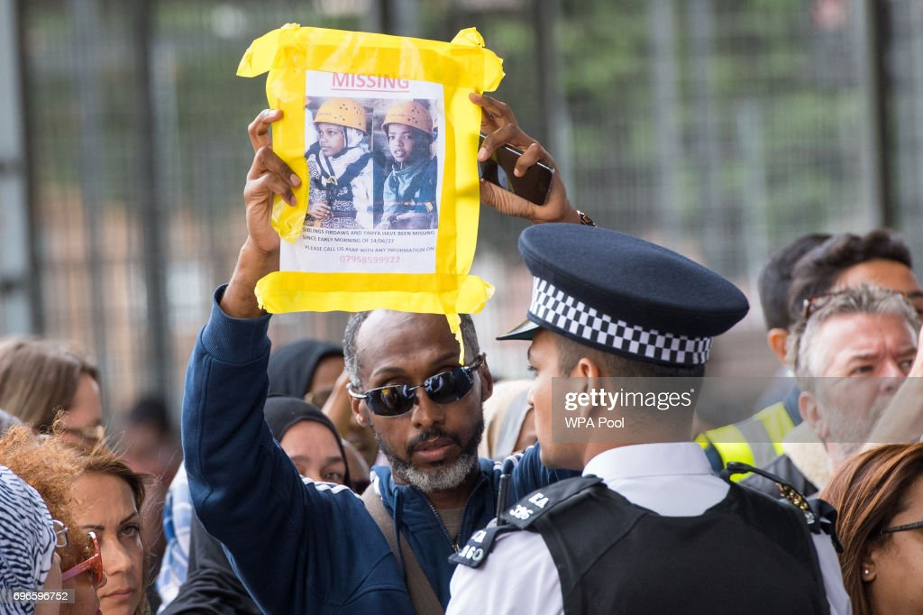 A man holds up a missing persons poster during a visit by Queen Elizabeth II and Prince William, Duke of Cambridge to the Westway Sports Centre, which is providing temporary shelter for those who have been made homeless in the Grenfell Tower disaster. on June 16, 2017 in London, England. 30 people have been confirmed dead and dozens still missing, after the 24 storey residential Grenfell Tower block in Latimer Road was engulfed in flames in the early hours of June 14. Emergency services will spend a third day searching through the building for bodies. Police have said that some victims may never be identified.