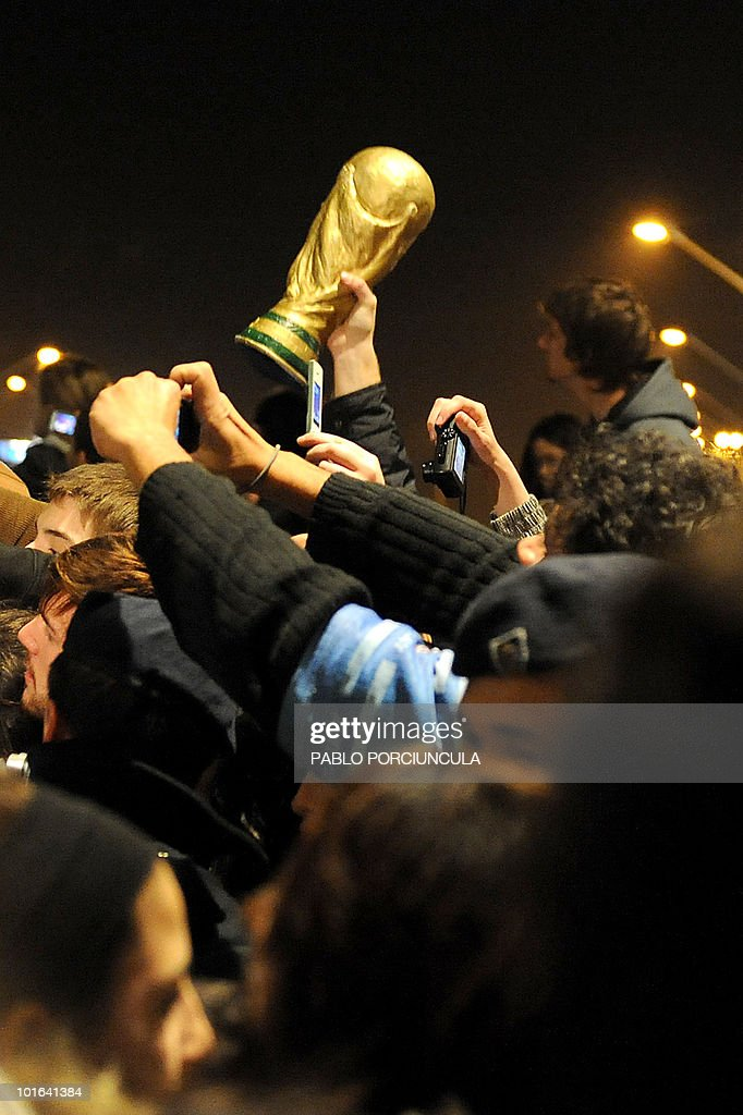 A man holds up a mock World Cup trophy as Uruguayan football supporters cheer the national football team players upon their arrival at Carrasco airport in Montevideo on June 5, 2010. The Uruguayan national football team departed to South Africa to participate in the FIFA World Cup South Africa 2010. AFP PHOTO/Pablo PORCIUNCULA