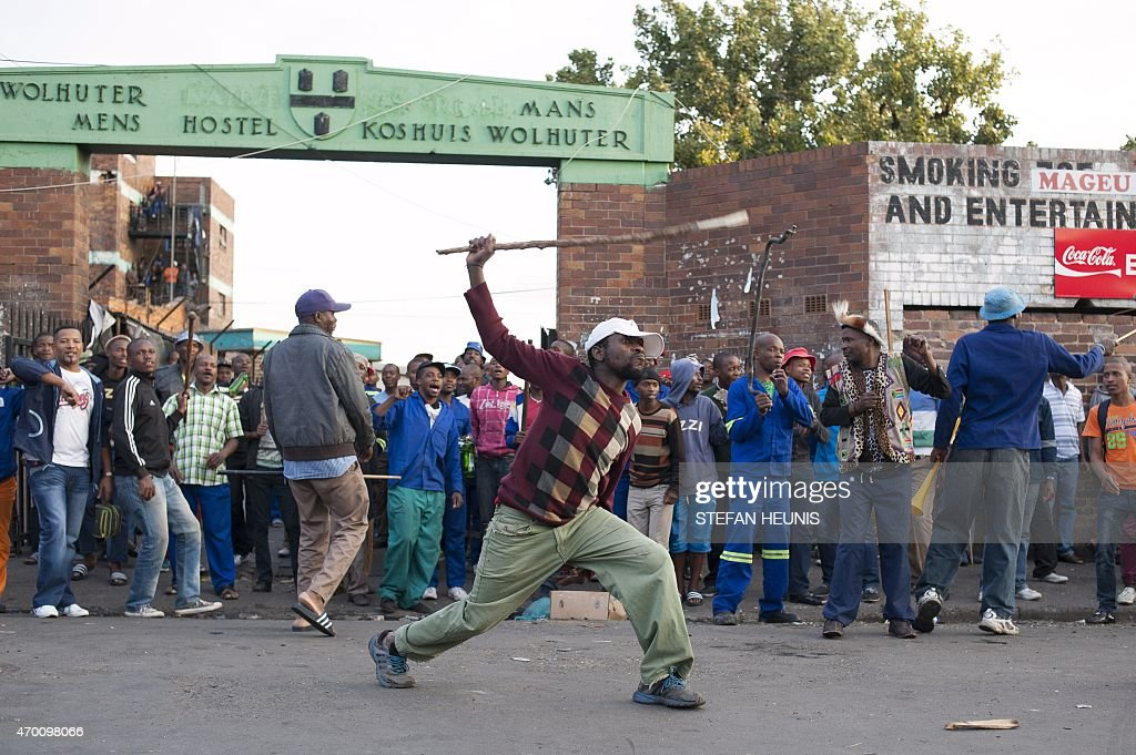 A man holds up a piece of wood as Zulu protesters demonstrate in front of their hostel in the Jeppestown district of Johannesburg on April 17 against...