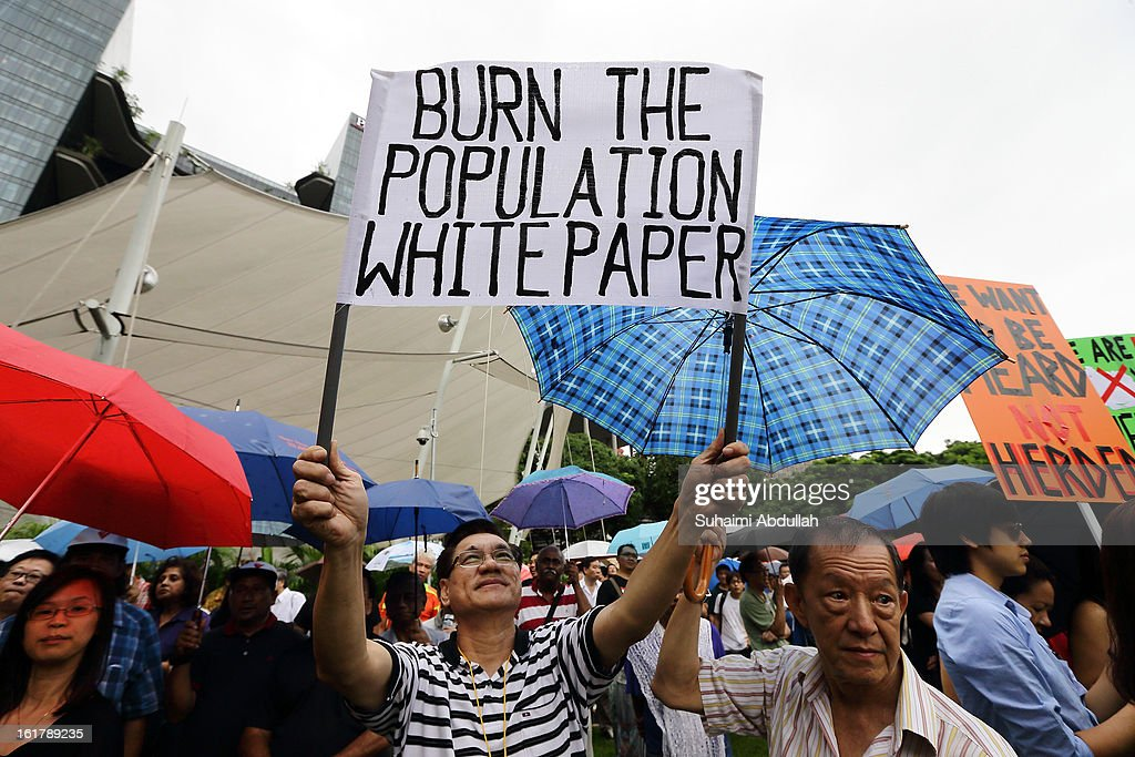 A man holds up a placard at Hong Lim Park to protest against the government's White Paper on Population at Speakers' Corner on February 16, 2013 in Singapore. Thousands of protesters gathered today following the release of a government white paper on population that revealed it could increase 30% to 6.9 million by 2030, angering residents who already see a strain on housing, transportation and healthcare.
