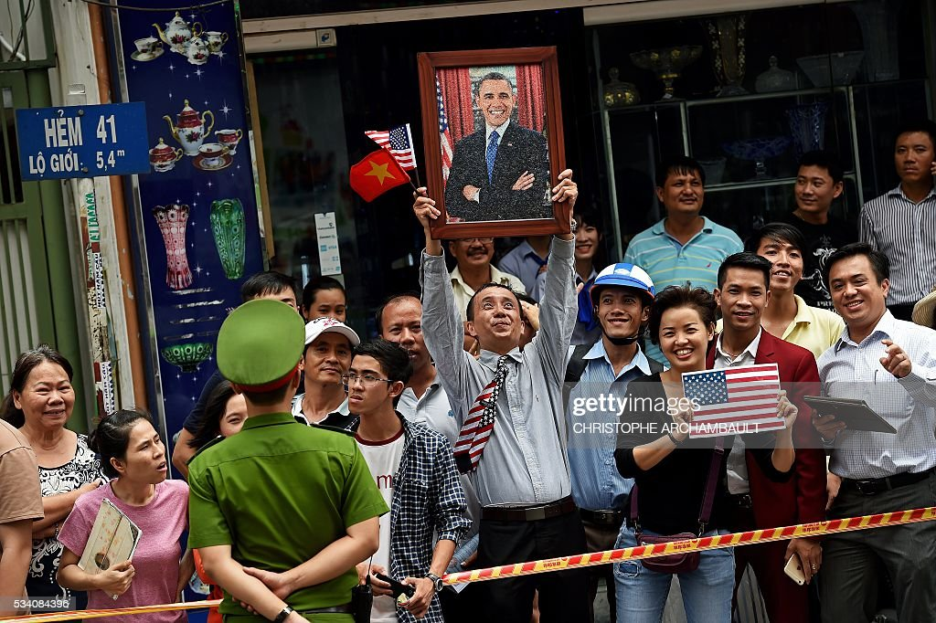 A man holds up a portrait of US President Barack Obama as people line up the streets to catch a glimpse of the US leader on his way to the airport at the end of two-day visit to Ho Chi Minh City on May 25, 2016. Obama fielded questions on May 25 on everything from rap and weed smoking to leadership and his good looks at a lively town hall-style meeting with young Vietnamese, who say the US leader is a far cry from their staid Communist rulers. / AFP / CHRISTOPHE