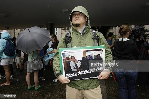 A man holds up a protest sign in Charter Garden at the start of the protest rally to support Edward Snowden in Hong Kong on June 15 2013 in Hong Kong...