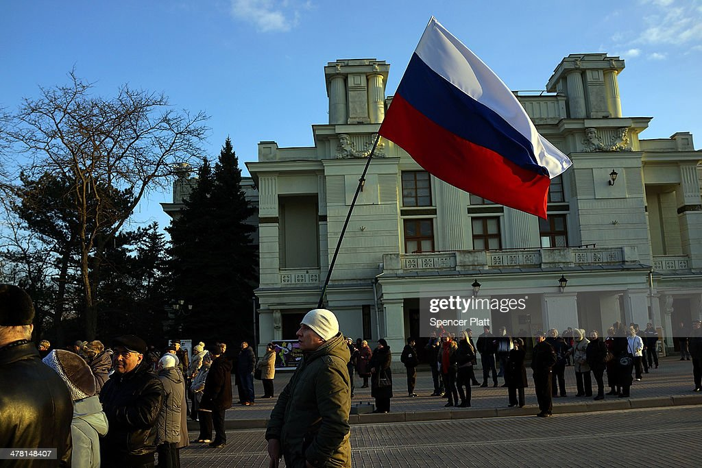 A man holds up a Russian flag at a rally in support of the upcoming referendum on March 12, 2014 in Yevpatoria, Ukraine. As the standoff between the Russian military and Ukrainian forces continues in Ukraine's Crimean peninsula, world leaders are pushing for a diplomatic solution to the escalating situation. Crimean citizens will vote in a referendum on 16 March on whether to become part of the Russian federation.