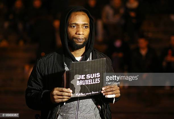 A man holds up a sign as a mark of solidarity as people leave tributes at the Place de la Bourse following today's attacks on March 22 2016 in...