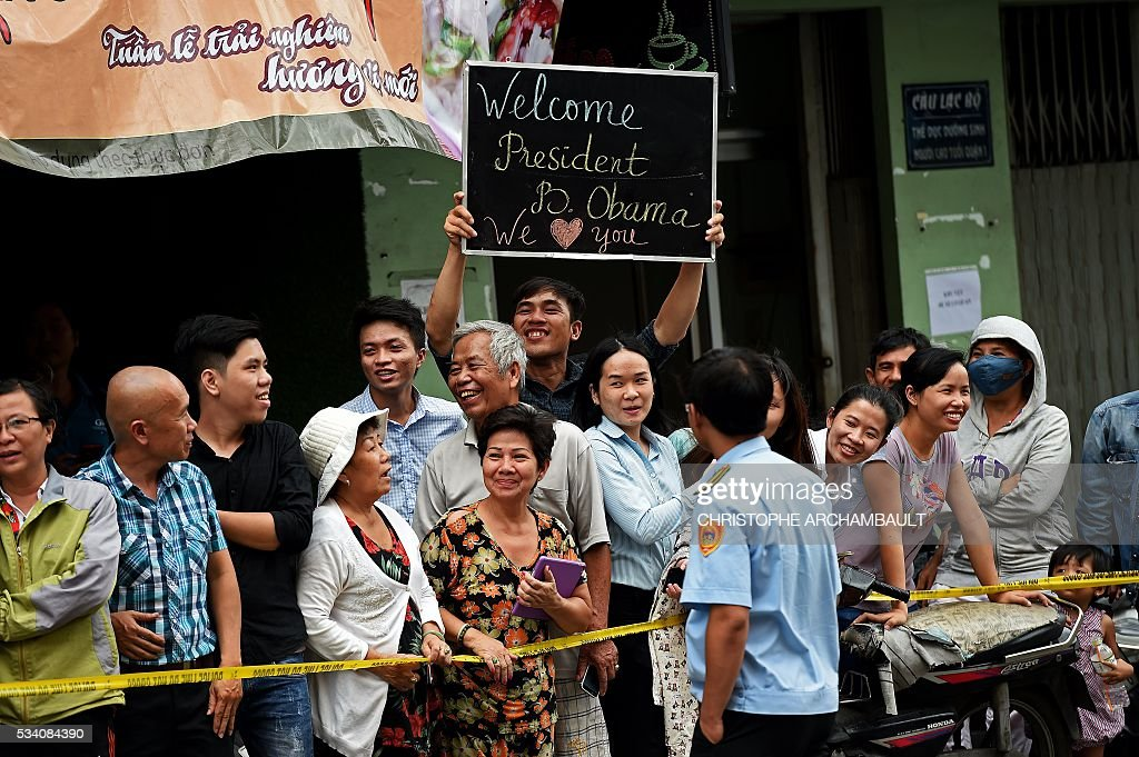 A man holds up a sign as people line up the streets to catch a glimpse of US President Barack Obama on his way to the airport at the end of two-day visit to Ho Chi Minh City on May 25, 2016. Obama fielded questions on May 25 on everything from rap and weed smoking to leadership and his good looks at a lively town hall-style meeting with young Vietnamese, who say the US leader is a far cry from their staid Communist rulers. / AFP / CHRISTOPHE