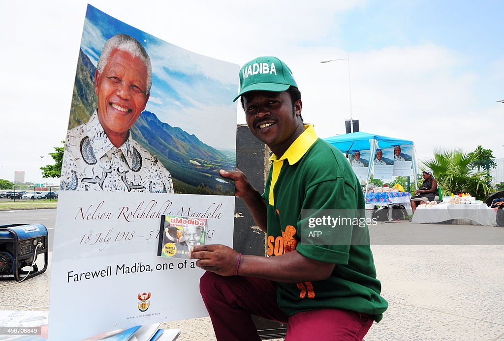 A man holds up a sign in honor of late former South African President Nelson Mandela as people watch a live television broadcast of his funeral ceremony, on the day of Mandela's burial in his hometown, on December 15, 2013, in Durban. Mandela was buried near his homestead Qunu today, ending 10 days of national mourning and global tributes for the prisoner-turned-president who transformed his country and inspired the world. AFP PHOTO / Anesh Debiky