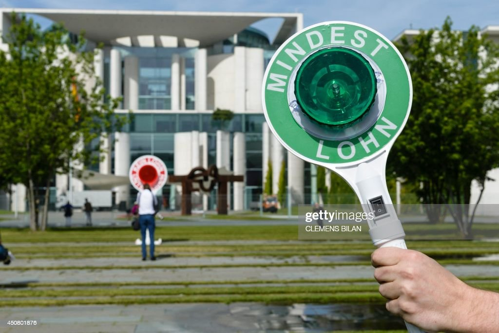 A man holds up a sign reading 'minimum wage' in front of the German parliament during the weekly cabinet meeting at the Chancellery in Berlin on June...