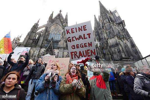 A man holds up a sign reading 'No violence against women' as he takes part in a demonstration in front of the cathedral in Cologne western Germany on...