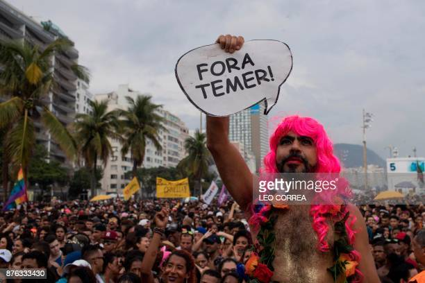 A man holds up a sign reading 'Out Temer' referring to Brazilian President Michel Temer as he attends the Gay Pride Parade at Copacabana beach in Rio...