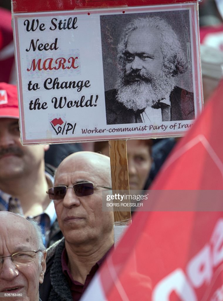 A man holds up a sign reading 'We still need Marx to change the world' during a May Day or International Workers' Day rally in Frankfurt am Main, central Germany, on May 1, 2016. / AFP / dpa / Boris Roessler / Germany OUT