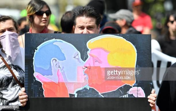 A man holds up a sign showing President Donald Trump kissing Russian President Vladimir Putin at a rally where Trump supporters and antiTrump...