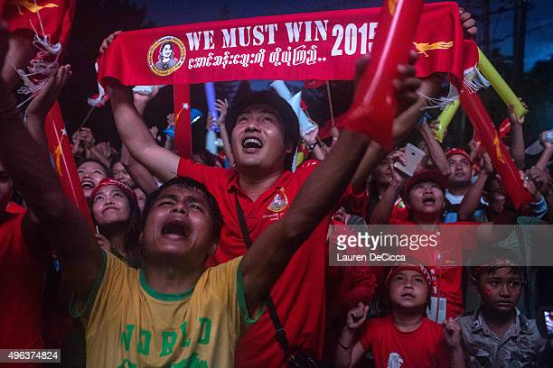 A man holds up a sign stating 'we must win' as crowds gather for the election result announcement in front of the National League for Democracy's...