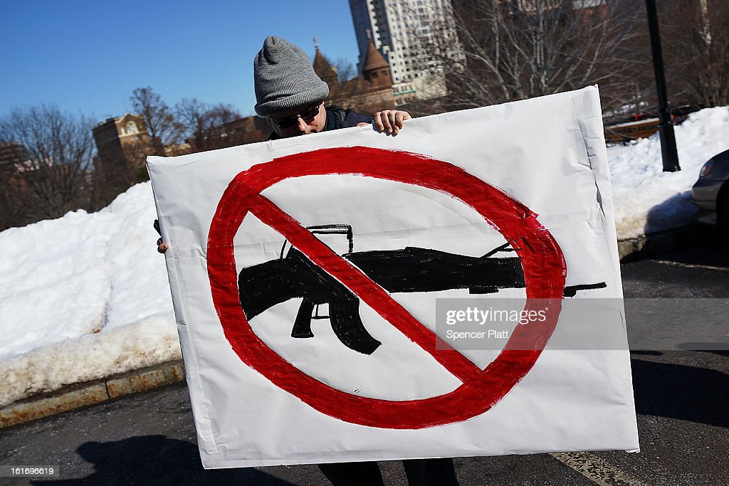 A man holds up a sign with with a depiction of an assault weapon during a rally at the Connecticut State Capital to promote gun control legislation in the wake of the December 14, 2012, school shooting in Newtown on February 14, 2013 in Hartford, Connecticut. Referred to as the 'March for Change' and held on the two-month anniversary of the massacre in Newtown, Connecticut, participants called for improved gun safety laws. Among the safety measures being demanded are for universal background checks, more work within the mental health community and restricting high-capacity magazines.