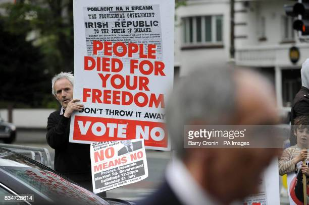 A man holds up a 'Vote No' sign as delegates meet with the French President Nicholas Sarkozy at the French Embassy in Dublin regarding the Lisbon...