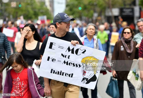 A man holds up an antiTrump sign during the March for Science in San Francisco California on April 22 2017 Day Thousands of people joined a global...