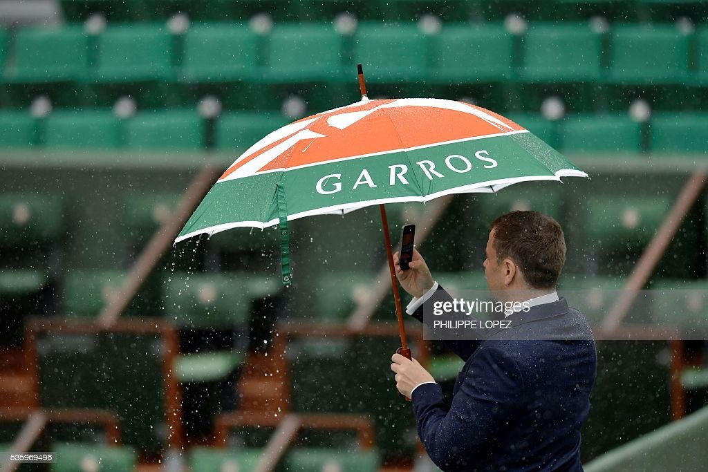 A man holds up an umbrella and takes a picture as rains falls over the Roland Garros stadium during the Roland Garros 2016 French Tennis Open in Paris on May 31, 2016. / AFP / PHILIPPE