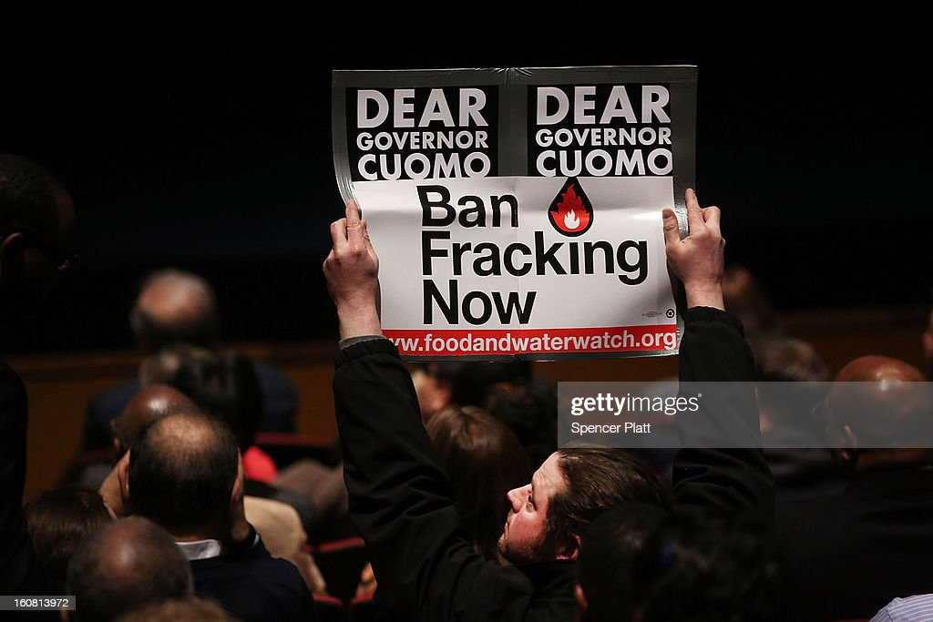 A man holds up and anti fracking sign as New York Governor <a gi-track='captionPersonalityLinkClicked' href=/galleries/search?phrase=Andrew+Cuomo&family=editorial&specificpeople=228332 ng-click='$event.stopPropagation()'>Andrew Cuomo</a> delivers his State of the State and budget proposals at The City College of New York on February 6, 2013 in New York City. Among issues addressed were the cost of the recovery from Hurricane Sandy, policing, economic development and education. His $142.6 million executive budget would increase state spending by 2 percent and raise school aid by 4.4 percent, to $21 billion.