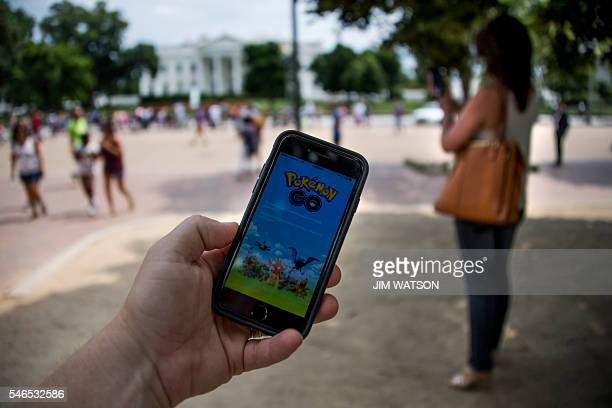 A man holds up his cell phone with a screen shot of the Pokemon Go game as a woman searches on her cell phone for a Pokemon in front of the White...