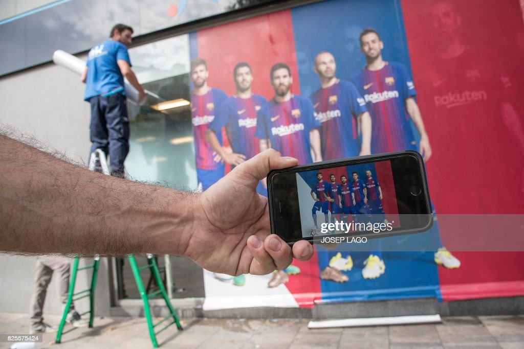 TOPSHOT - A man holds up his mobile phone with a photo of a poster featuring Barcelona's Brazilian forward Neymar (2nd R) after it was replaced with another poster (back) outside the Camp Nou Stadium in Barcelona on August 2, 2017. Neymar could be presented as a Paris Saint-Germain player as early as this weekend for a world record fee as Barcelona admitted defeat in convincing the Brazilian to stay at the Camp Nou on August 2. / AFP PHOTO / Josep LAGO