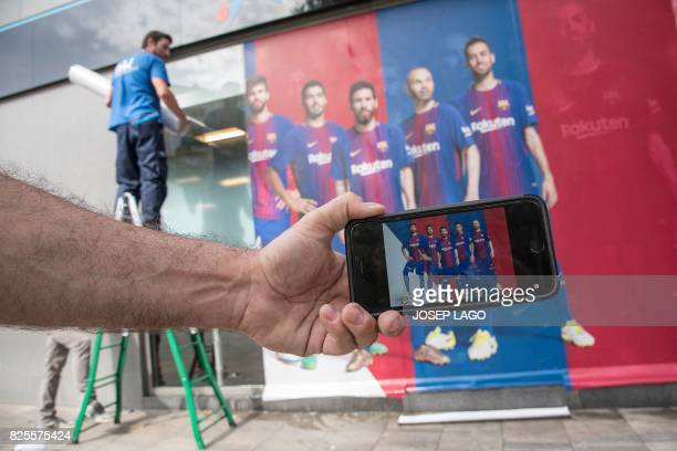 TOPSHOT A man holds up his mobile phone with a photo of a poster featuring Barcelona's Brazilian forward Neymar after it was replaced with another...
