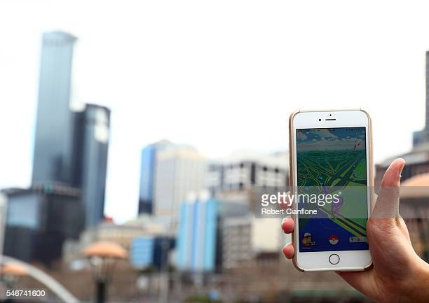 A man holds up his phone as he plays the Pokemon Go game on July 13 2016 in Melbourne Australia The augmented reality app requires players to look...
