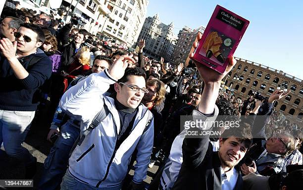 A man holds US author Charles Bukowski's book 'La Maquina de Follar' as he attends a demonstration in Valencia on February 21 2012 The demonstrators...