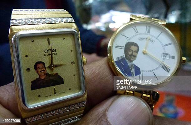 A man holds watches bearing the portrait of late Iraqi dictator Saddam Hussein on December 9 2013 at a market in Baghdad In a predominantly Shiite...