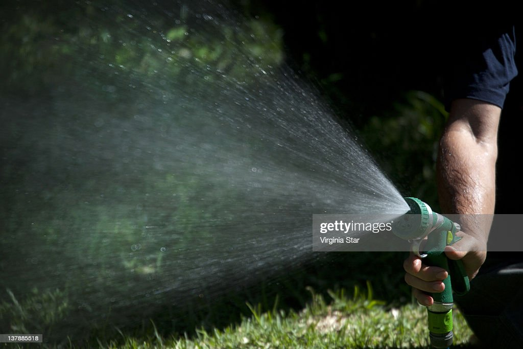 Man holds water spray gun hose