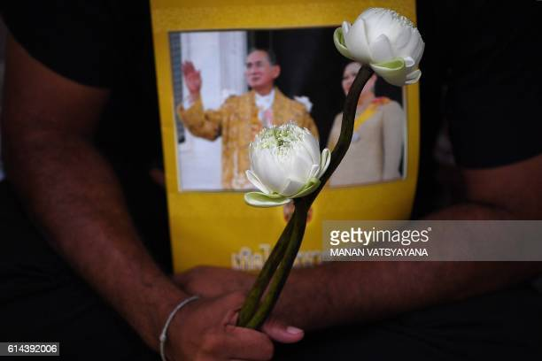 TOPSHOT A man holds white flowers and a portrait of Thailand's King Bhumibol Adulyadej at Siriraj Hospital in Bangkok early October 14 2016 King...