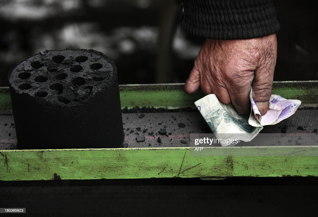 A man holds yuan notes next to a coal briquettes, at a coal distribution business in Huaibei, central China's Anhui province on January 30, 2013. Environmental concerns -- particularly over the use of coal -- have been pushed to the top of the agenda after much of the country was covered with a blanket of pollution this past month. The air quality index (AQI) from the Beijing Municipal Environmental Monitoring Centre reached 993 during the worst of the pollution, almost 40 times the World Health Organisation's recommended safe limit. CHINA OUT AFP PHOTO