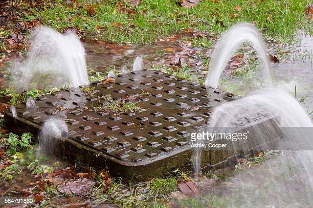 A man hole cover being pushed up under the force of water pressure during flooding in Ambleside, Lake District, UK.