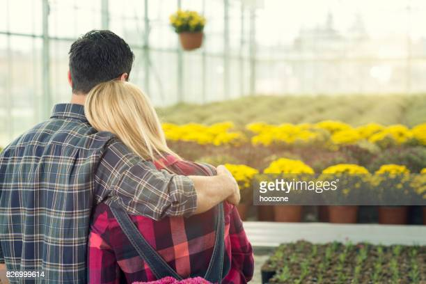 Man holnding women and looking at flowers at greenhouse.
