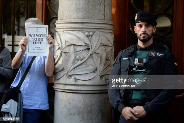 A man holds proreferendum poster next to a Spanish Civil Guard who stands in front of the Economy headquarters of Catalonia's regional government in...