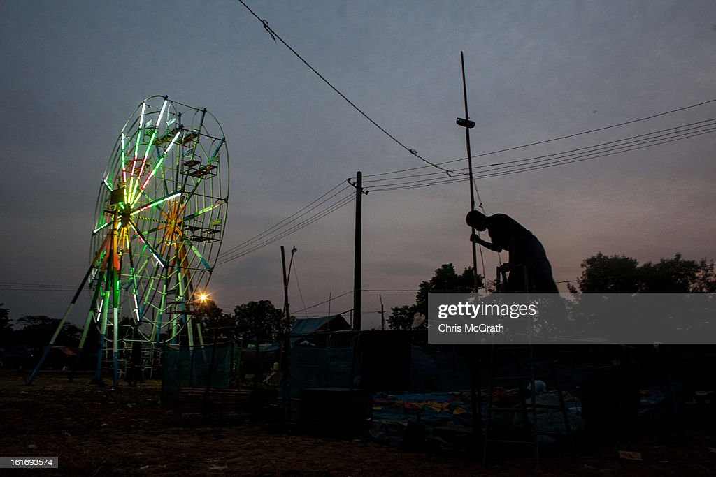 A man hooks up power at a traveling carnival site at South Dagon Township on February 14, 2013 in Yangon, Burma. Myanmar is going through rapid political and economic reforms initiated by the countries first civilian president Thein Sein after years of military junta rule.